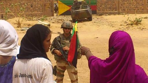 er unge Tuareg kvinner vifter med flaggene til Azawad foran en fransk soldat som står vakt foran en leir til de maliske militære avvist av Kidal's sivilbefolkningen.